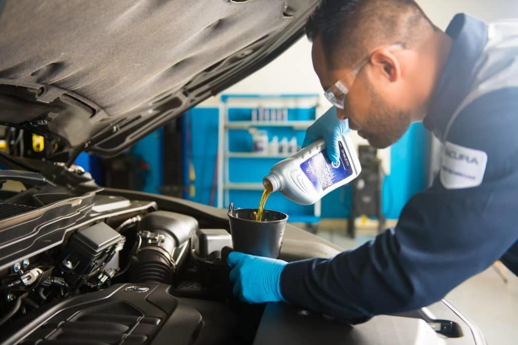 Acura Technician Adding Oil to a Car