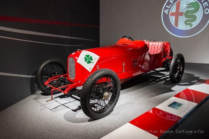 Red 1923 rl Alfa Romeo race car with hand-painted cloverleaf on display with black wheels
