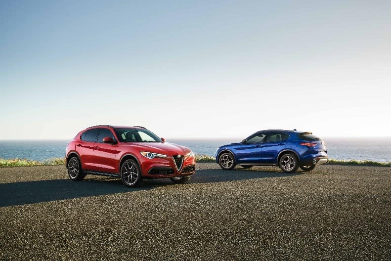 Two 2018 Alfa Romeo Stelvio Ti models in red and blue overlooking the ocean