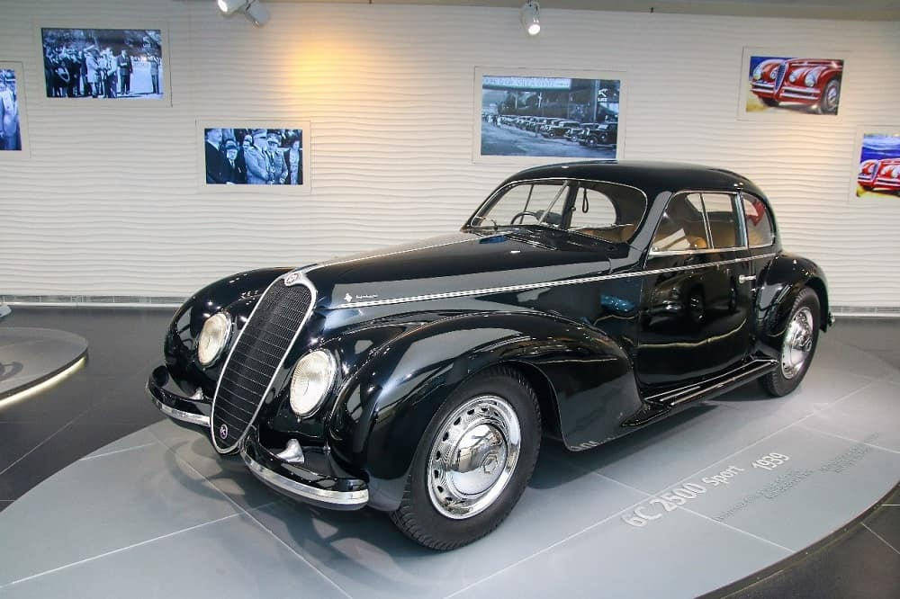 Black 1946 Alfa Romeo 6C 2500 two-door car with classic Italian styling on display in an automotive museum
