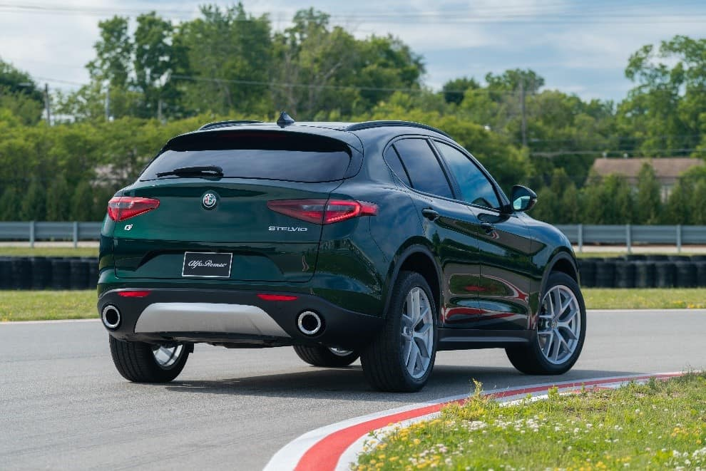Dark green 2019 Alfa Romeo parked on a curve of a track with green grass and trees