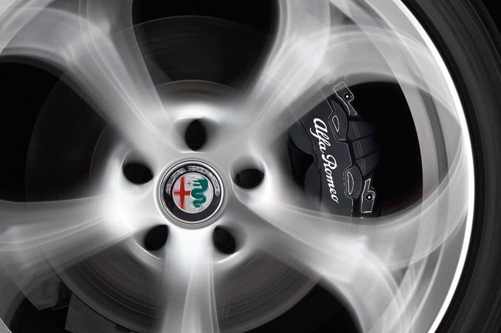 Gloss-black colored brake caliper behind light chrome 5-hole Alfa Romeo rim