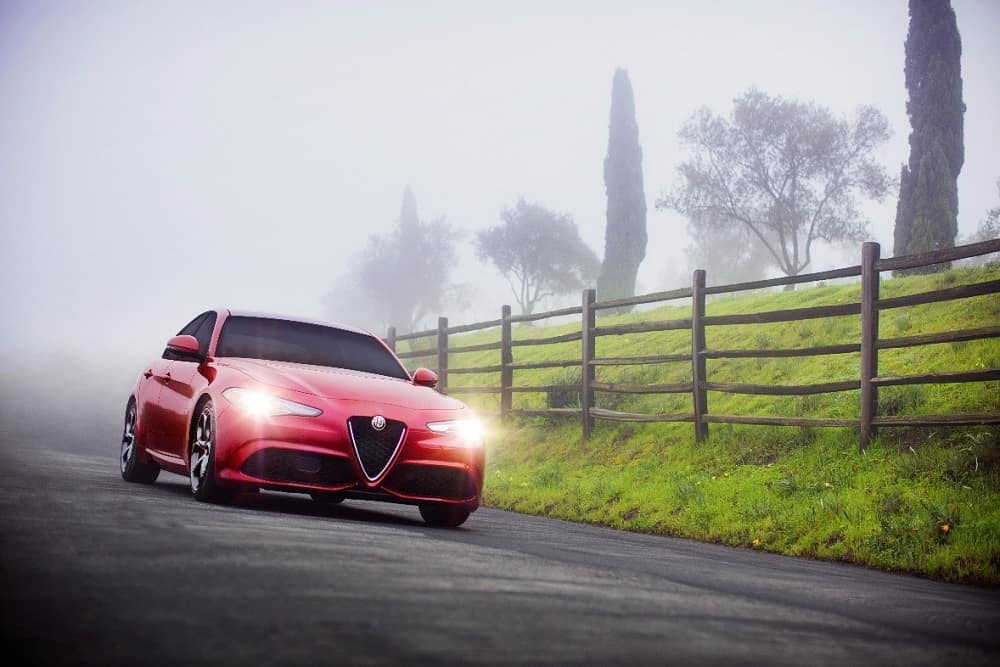 Red 2018 Alfa Romeo Giulia Ti Sport driving through fog on a country road with its daytimerunning lights turned on