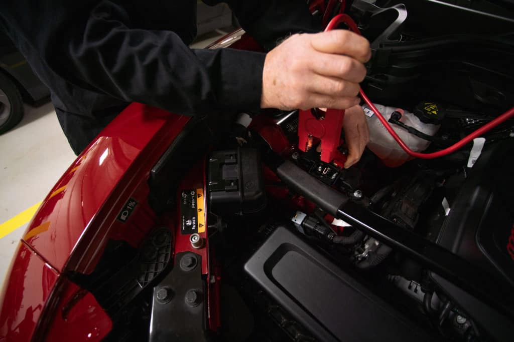 person connecting the positive end of a jumper cable to a positive battery terminal in an Alfa Romeo Giulia to jump-start the dead battery