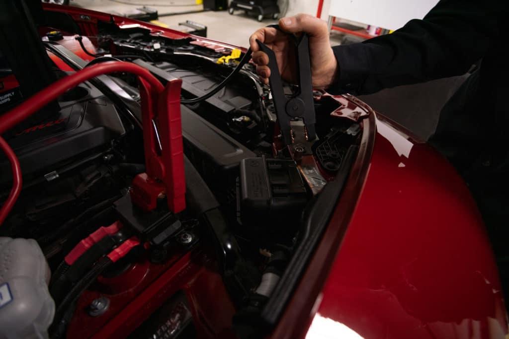 man connecting the negative end of live car battery to the negative end of a dead car battery to jump-start a red Alfa Romeo Giulia with jumper cables