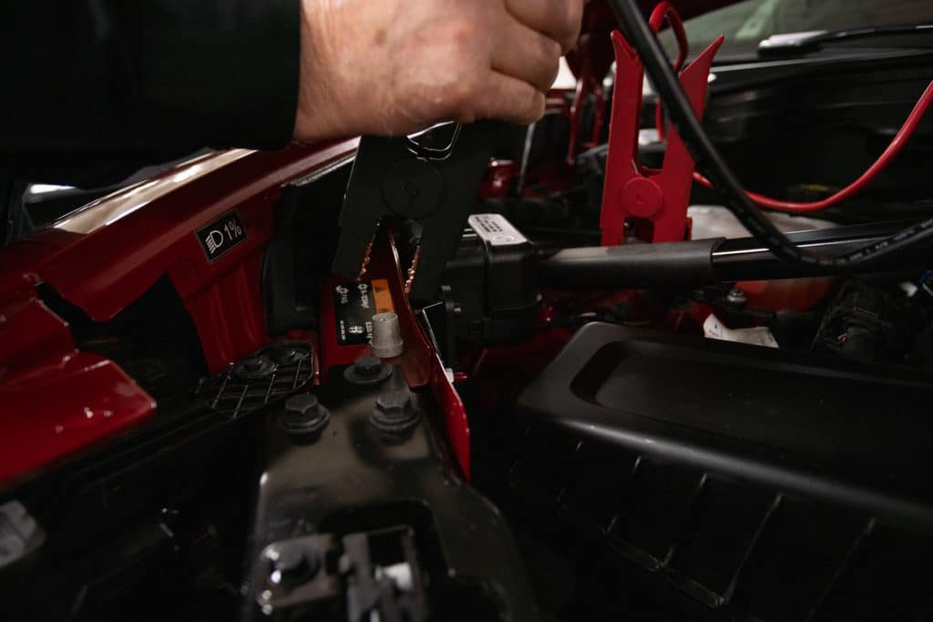 man connecting the negative end of a car battery jumper cable to an Alfa Romeo Giulia to jump-start the vehicle's dead battery