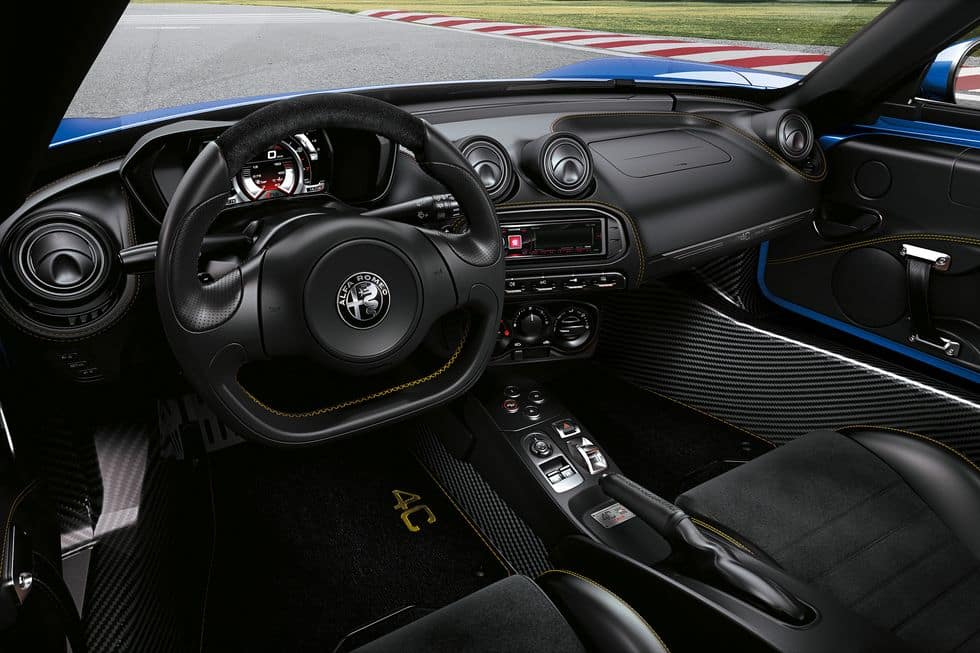 interior of a 2020 Alfa Romeo 4C Spider sportscar with black seats and a black leather-wrapped steering wheel