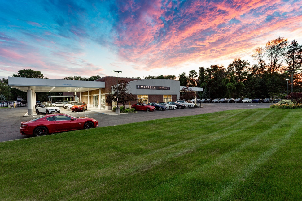 exterior picture of the Alfa Romeo of Albany and Maserati dealership with a blue and red sunset