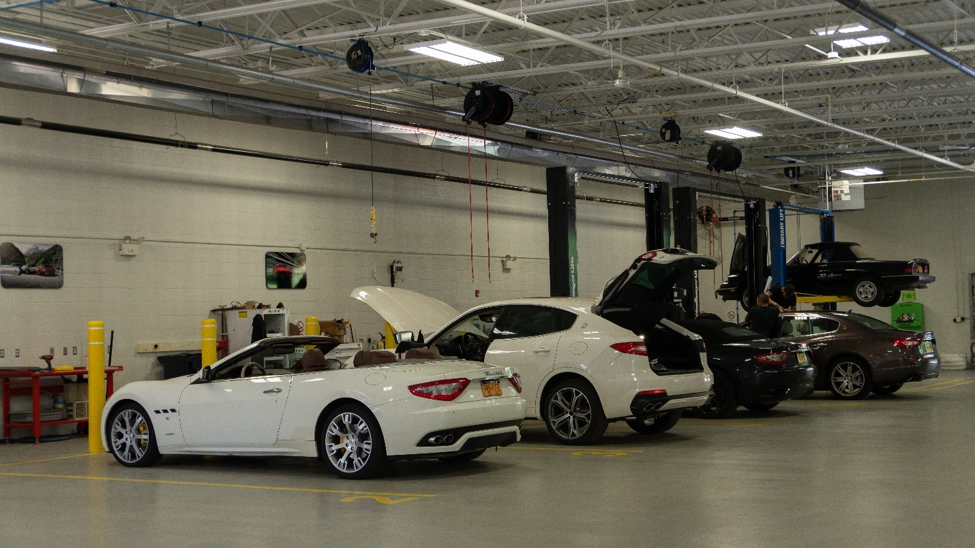 interior of the Alfa Romeo service center showing five high-end luxury cars receiving service from technicians