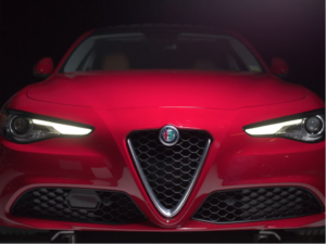 closeup shot of the frontend of a new Alfa Romeo Giulia sports car with a black grille and headlights turned on
