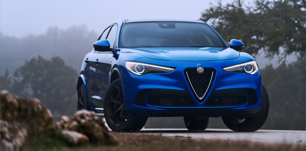 blue 2020 Alfa Romeo Quadrifoglio luxury SUV with black aluminum wheels and headlights turned on parked on a road near trees on an overcast day