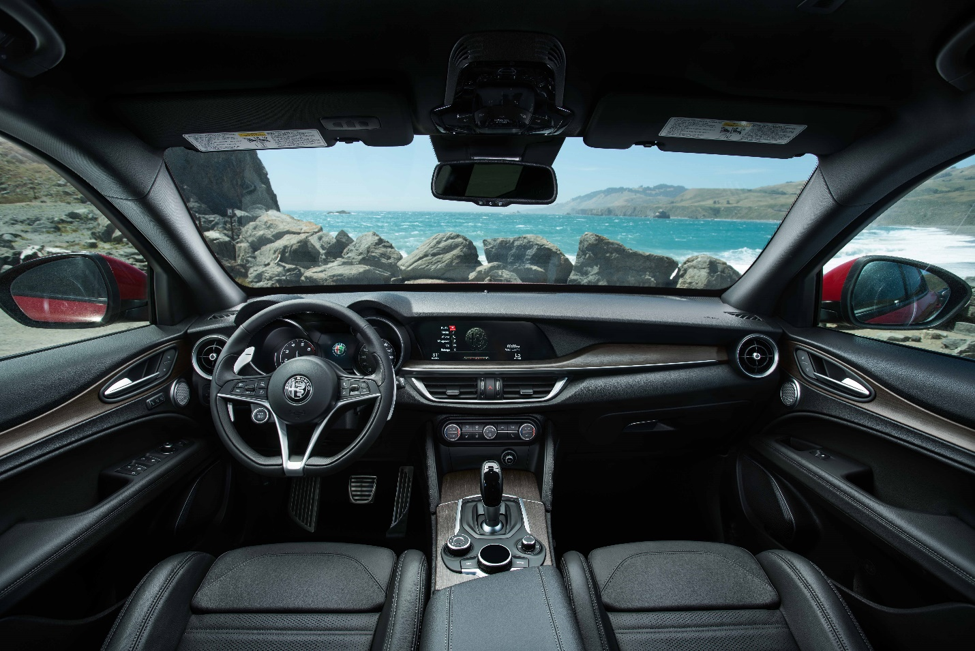 interior of a 2018 Alfa Romeo Stelvio with black leather upholstery, chrome, and wood accents