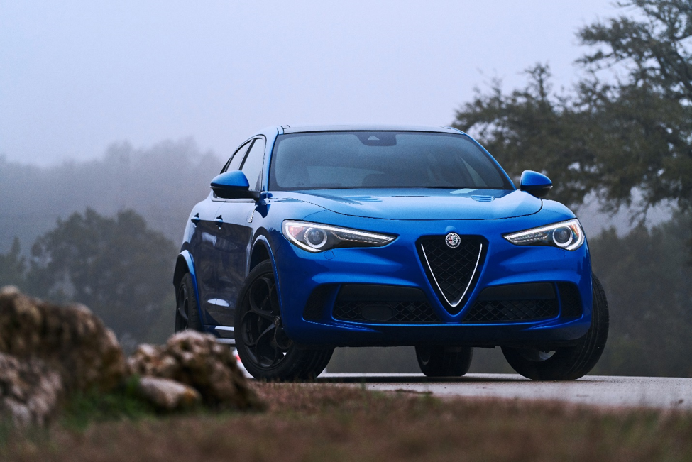 blue 2019 Alfa Romeo Stelvio parked on a paved road surrounded by trees with a gray-blue sky in the background
