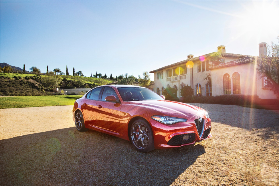 red 2018 Alfa Romeo Gilulia parked in front of a white stucco house with green grass and trees in the background