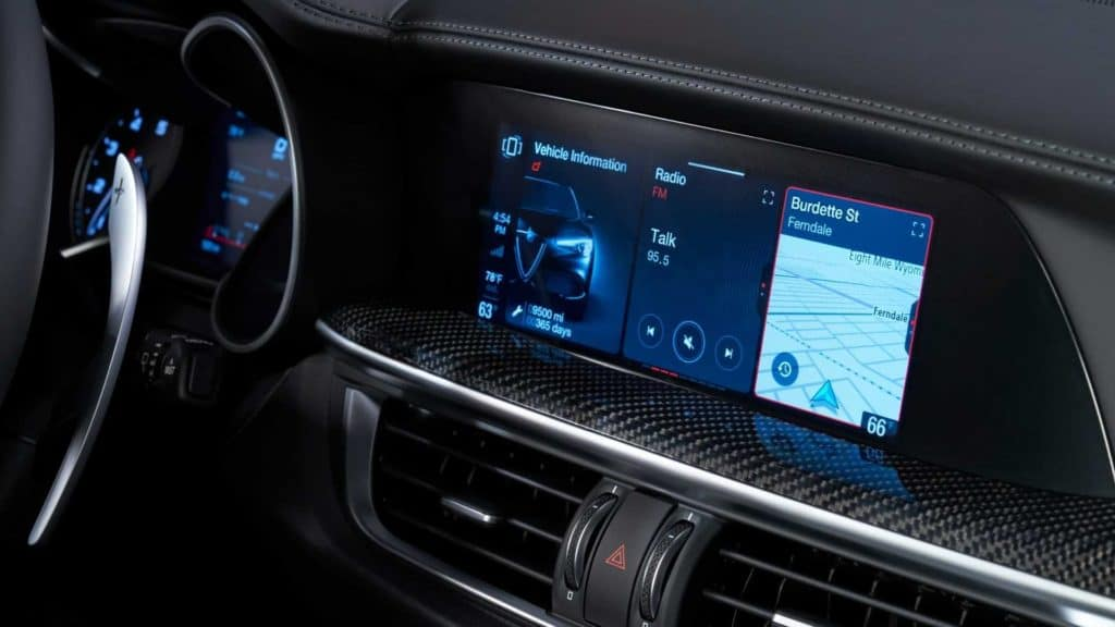 closeup of the infotainment center in a 2020 Alfa Romeo Stelvio dashboard interior displaying vehicle information, a radio station, and navigation details surrounded by black leather and chrome details