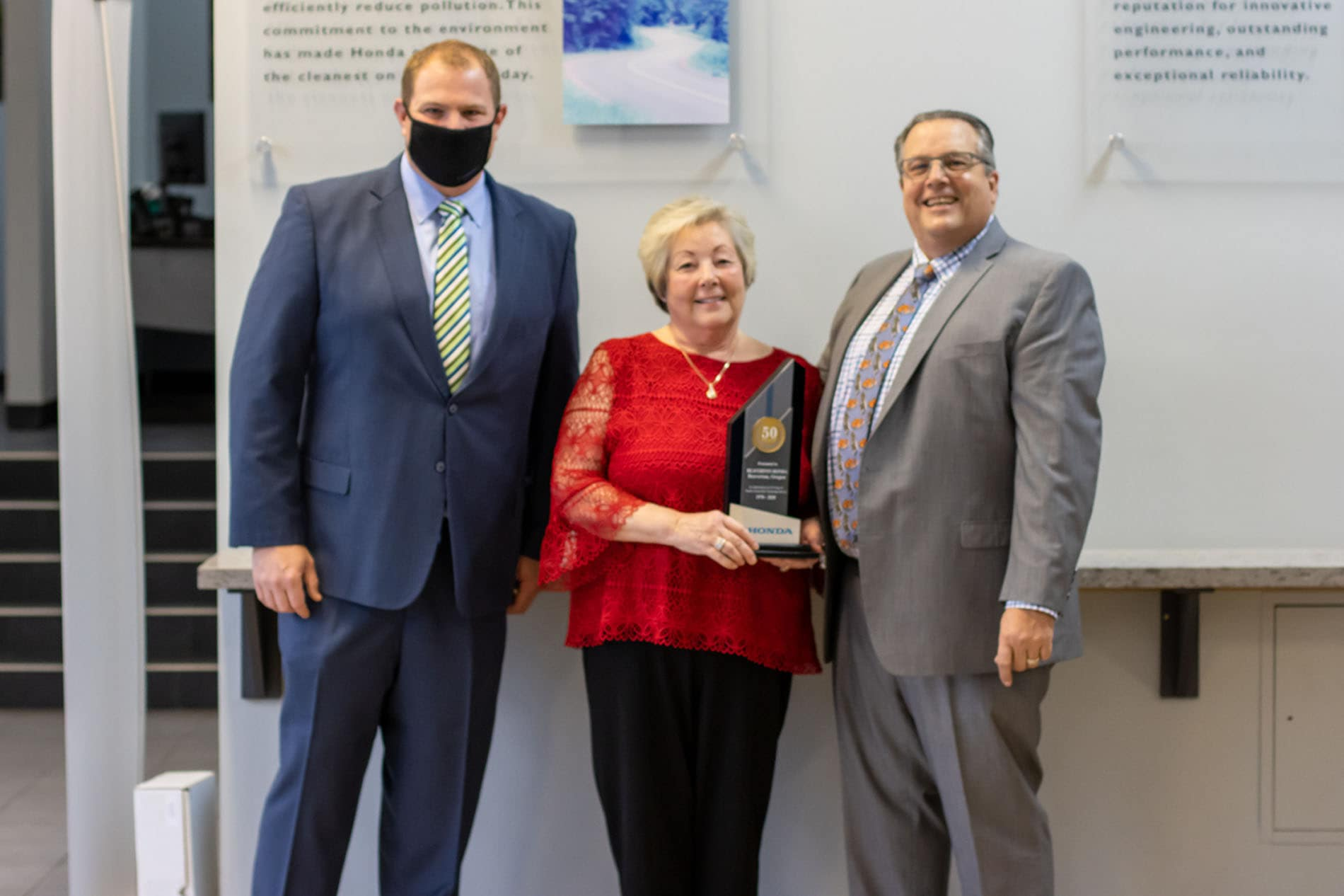 Honda representative, Don Laine, stands with owners, Sharon Lenz and Bob Lanphere, Jr holding the fifty years as a Honda Dealer Award at Beaverton Honda in Oregon