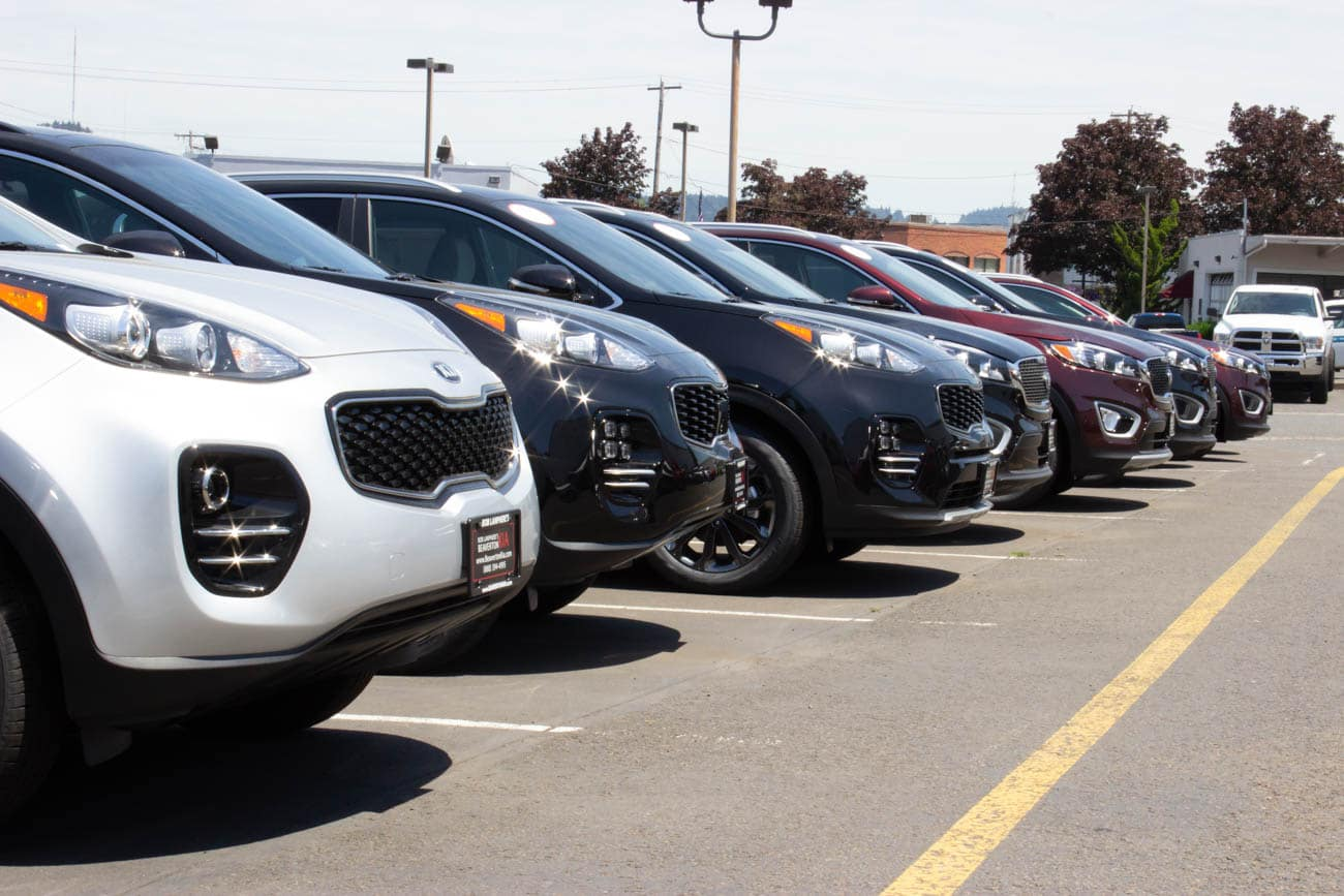 Line of new Kia models with posted price stinker on the windows at Beaverton Kia