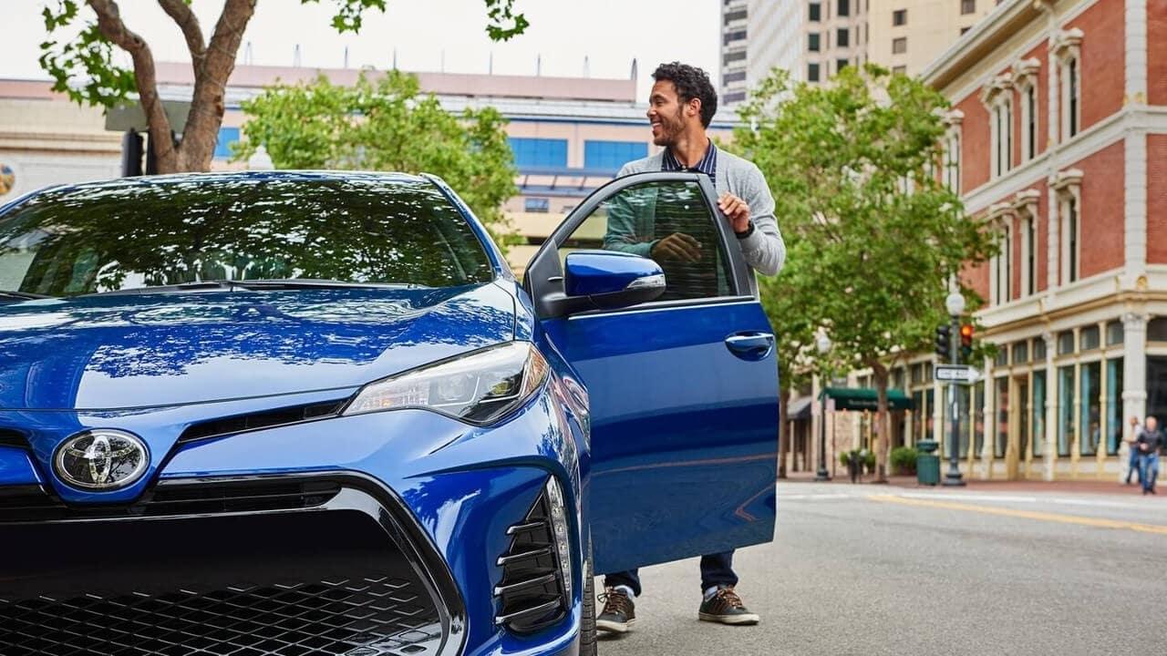 Man getting into Toyota Corolla