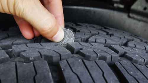 Person measuring tire depth