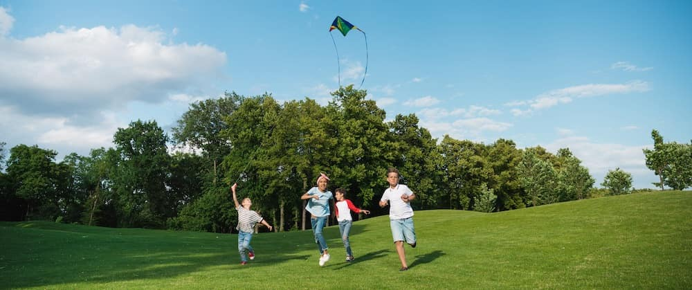 Children flying a kite and running in a park