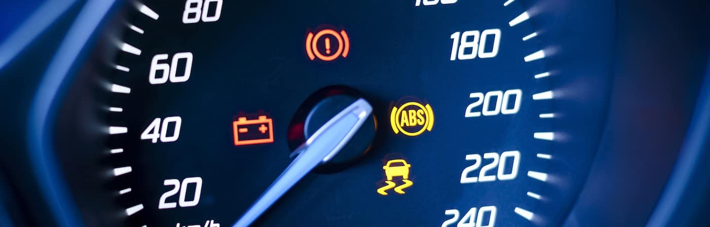 Photo presents vehicle's speedometer or tachometer with visible information display - ignition warning lamp and brake system warning lamp, visible symbols of instrument cluster ( ten check warning light), with warning lamps illuminated.