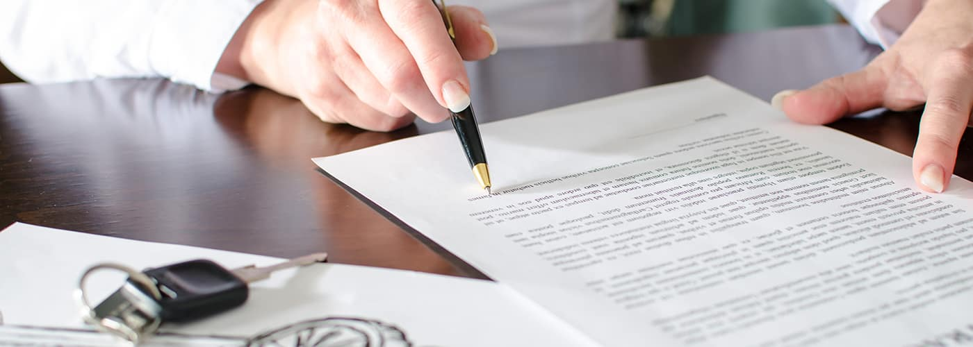 Woman reading a car purchase contract in car dealership