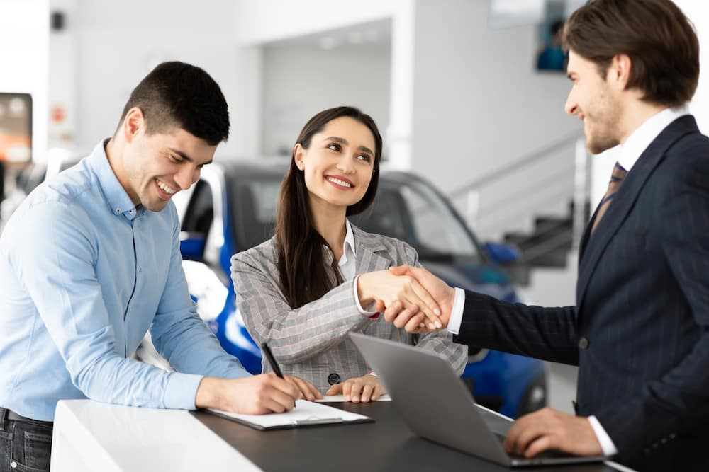 Spouses Buying Car And Handshaking With Seller Man