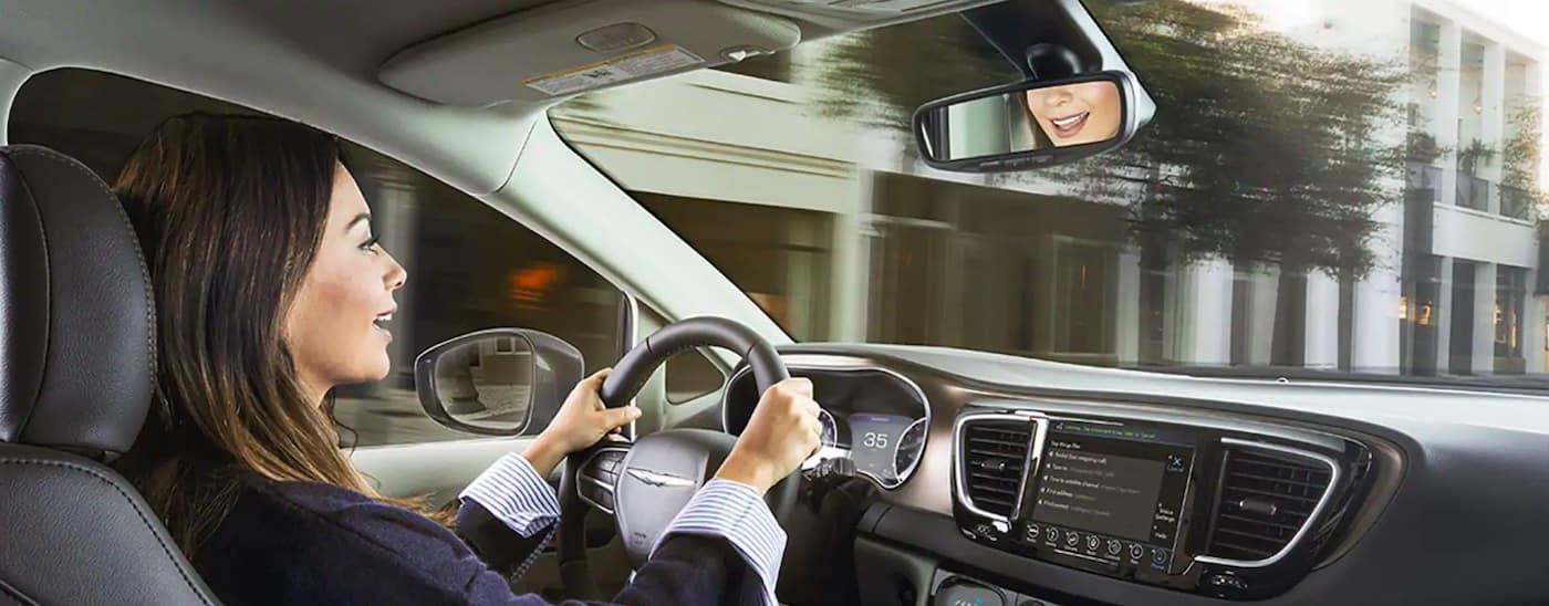 Woman using Uconnect system in Chrysler vehicle