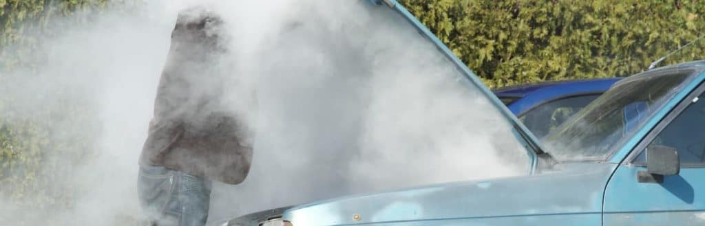 Blue Car overheating and blowing smoke in man's face