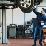 Man Checking Car in Service Bay