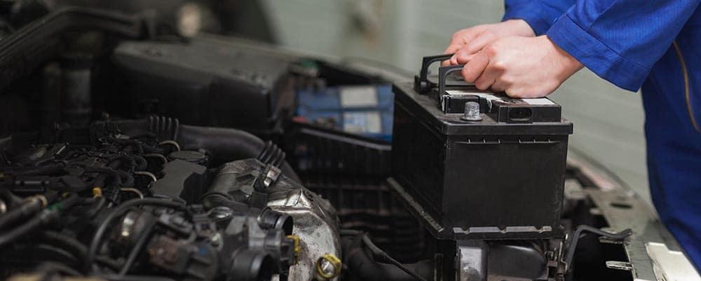 Male mechanic changing car battery