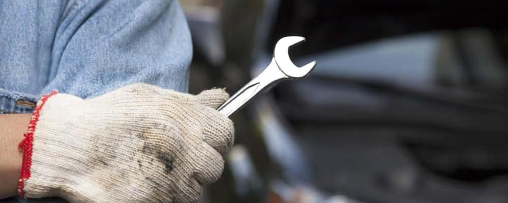 Man-with-glove-holding-a-wrench_15331853_xl-2015-8-e1544541636743 copy