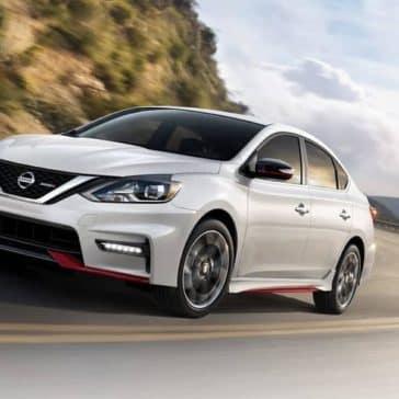 White-2019-Nissan-Sentra-driving-around-corner