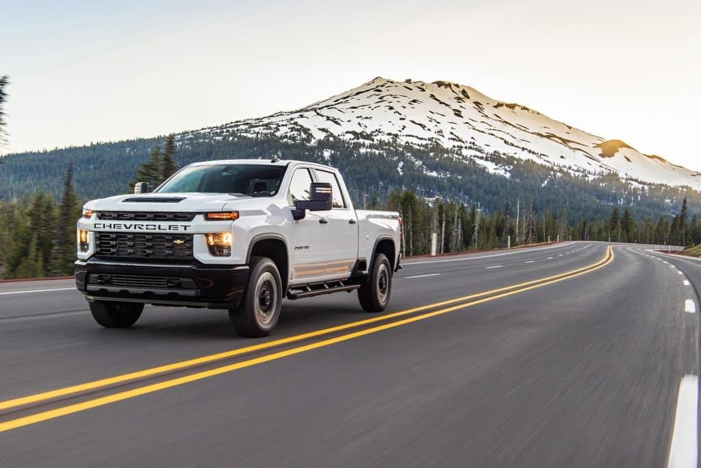 White 2020 Chevrolet Silverado 2500HD driving on a mountain freeway