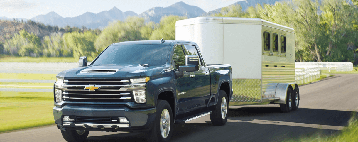 2020 Chevy Silverado 2500HD towing a trailer on rural road
