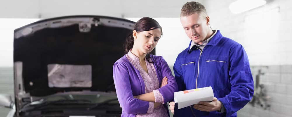 Male car mechanic shows clipboard of services to woman in purple with her car in background