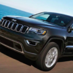 Black 2019 Jeep Grand Cherokee towing boat on highway next to lake