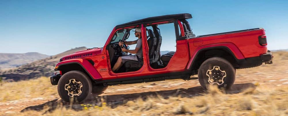 Red 2020 Jeep Gladiator with doors off driving off road