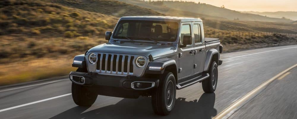 Silver 2020 Jeep Gladiator driving on highway at sunrise
