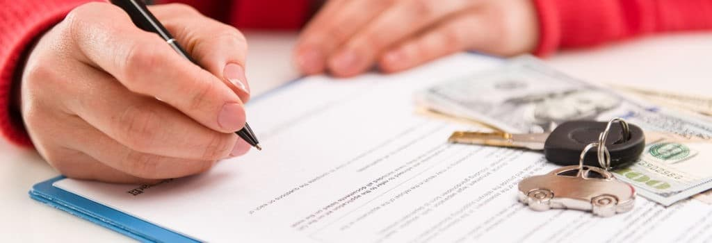 Hands of someone filling out finance application for car