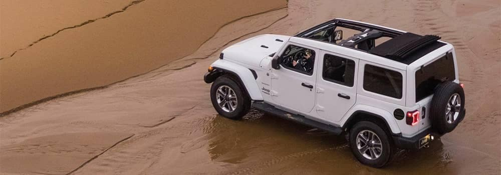 White Jeep Wrangler driving on sand