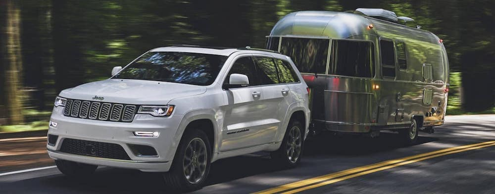 White 2020 Jeep Grand Cherokee towing a silver trailer on wooded road with blurred tree background