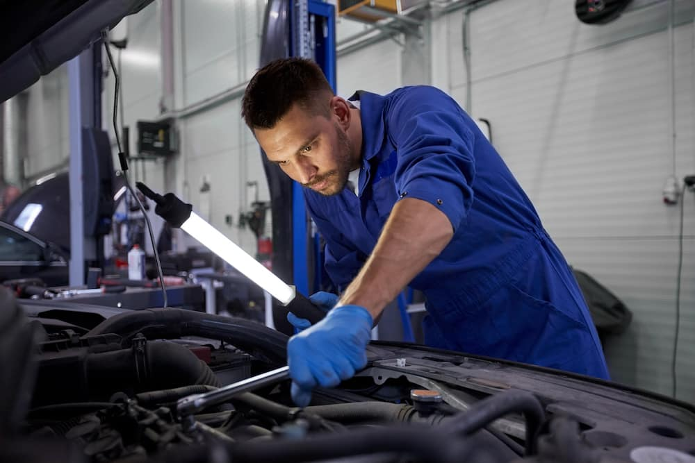 Car mechanic wearing blue looking at engine with lamp and wrench