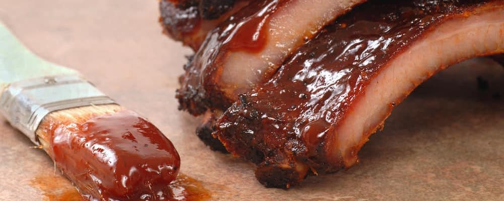 Close up of BBQ ribs with bbq brush nearby