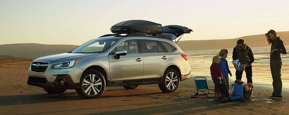 Family at a beach with their 2018 Subaru Outback parked on the sand