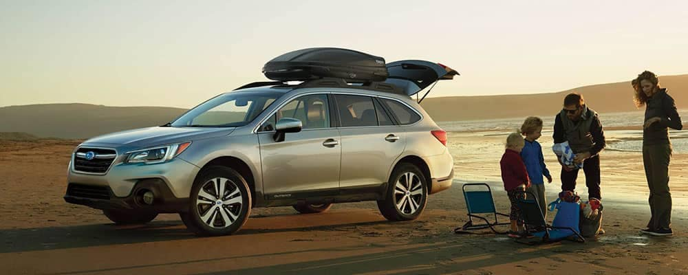 2018 Subaru Outback parked at the beach with a family standing by