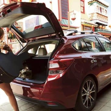 Woman Loading Guitar Into Cargo Area of 2019 Subaru Impreza 5-Door