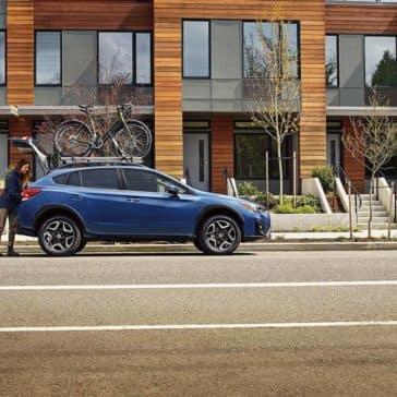 Couple Loading Cargo Area of 2019 Subaru Crosstrek Parked Outside Condos