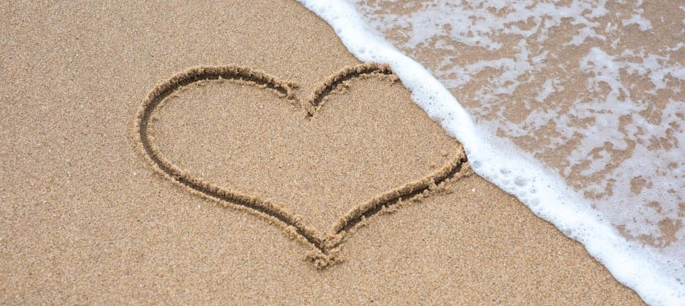 Beach with heart on it and wave approaching heart
