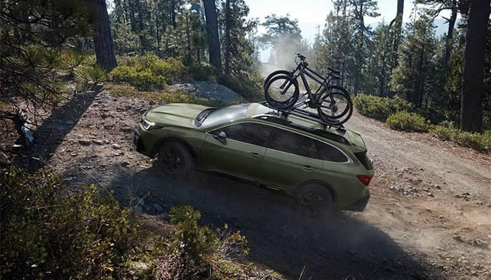 Subaru Outback off-roading in woods with bikes on roof